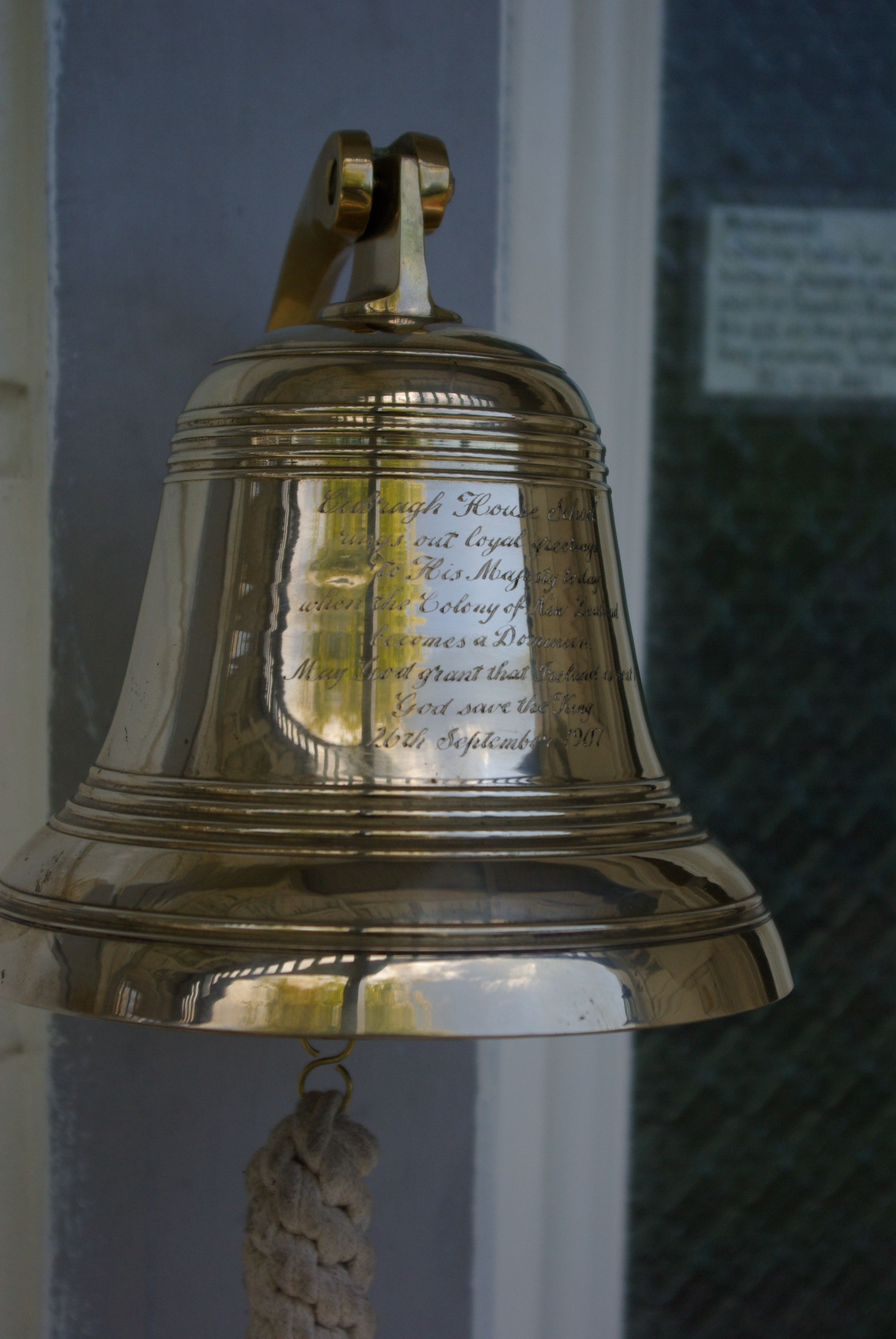 The 1907 brass bell from Cabragh House School that hangs at the door of Amber House Bed and Breakfast in the Nelson-Tasman region of the South Island of New Zealand